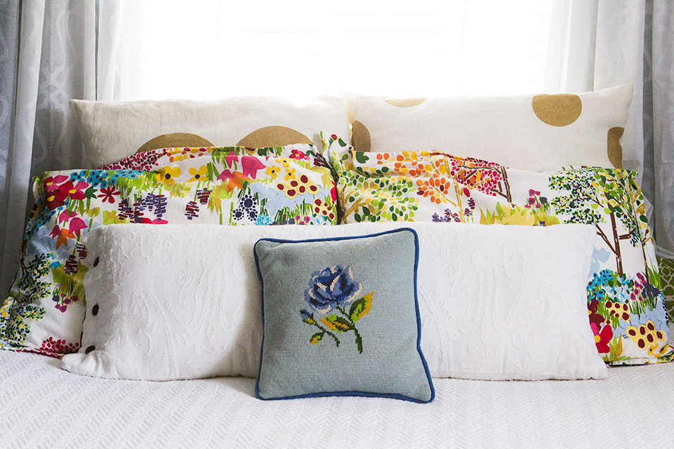 Floral and white bedding pop against the deep teal walls in this simple guest room.