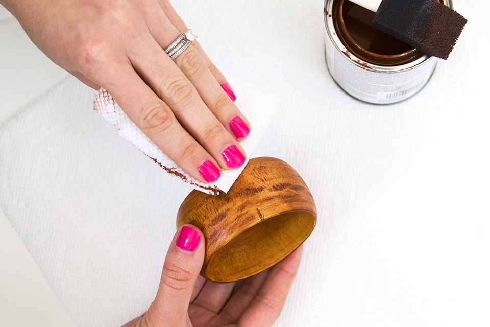 Use a paper towel to remove excess wood stain to create stained wood bangles.