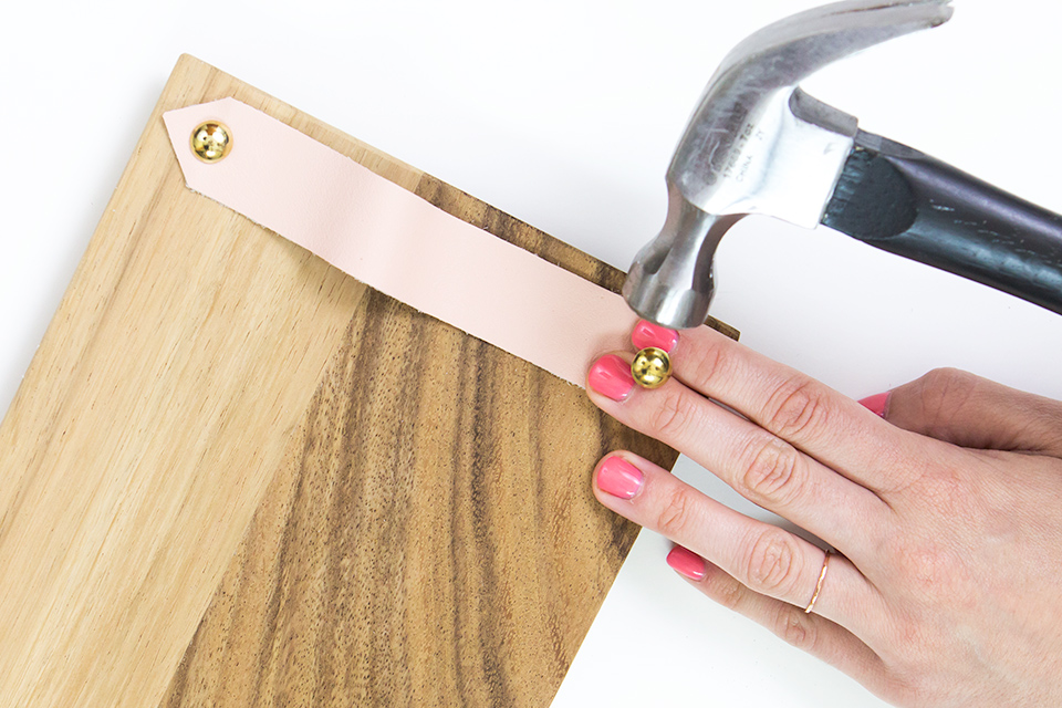 Attach a strip of leather to a wood board using brass furniture tacks. Such an easy way to make a stylish cheese board.