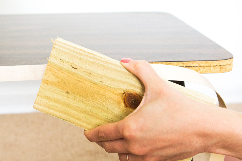 Use a scrap piece of wood to firmly press down the edging take tape after you iron it to make sure it adheres to the laminate or wood.