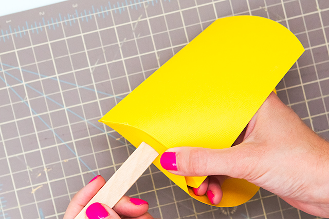 Insert wood sticks in the bottom of a pillow box to turn it into a popsicle treat box.