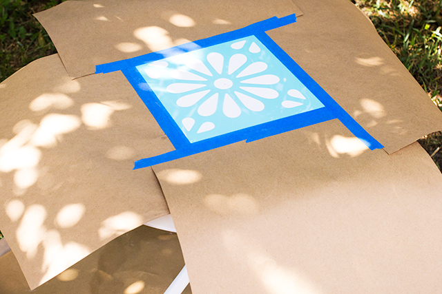 Use kraft paper to mask off the area around a stencil when using spray paint.