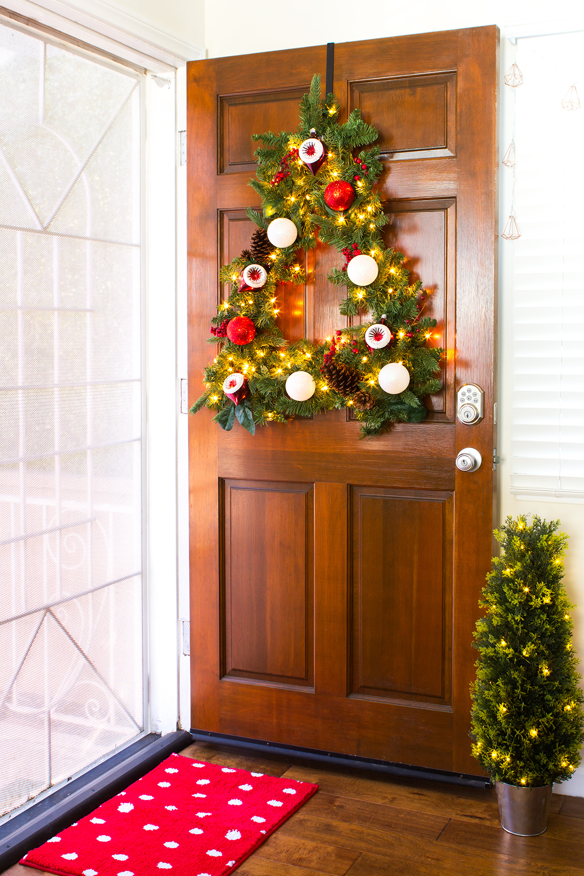 You can easily create a Christmas tree shaped wreath for your front door! Click through for the tutorial!