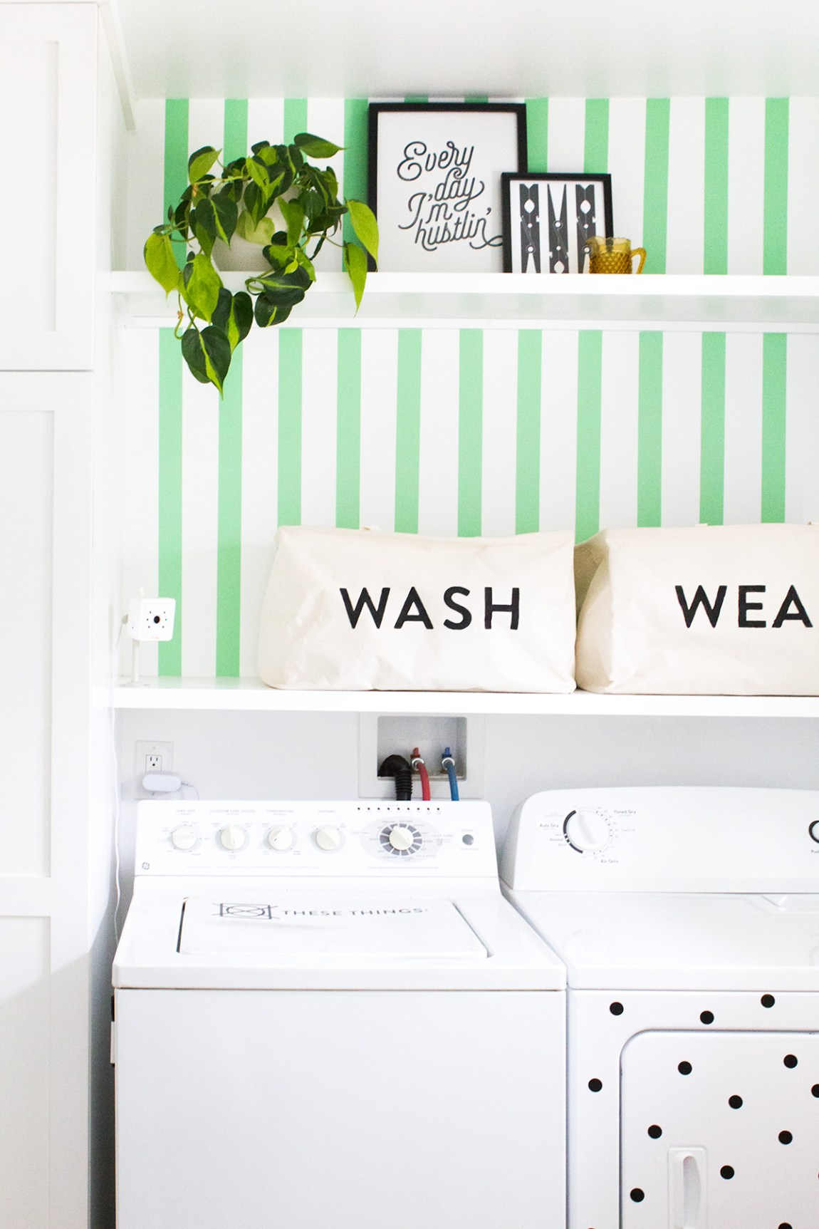 Loving how wide washi tape was used to create a faux-wallpaper accent wall in this tiny laundry nook.