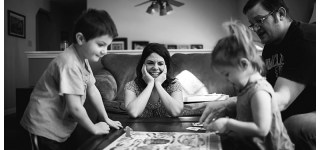 Family playing a board game during documentary family portrait session