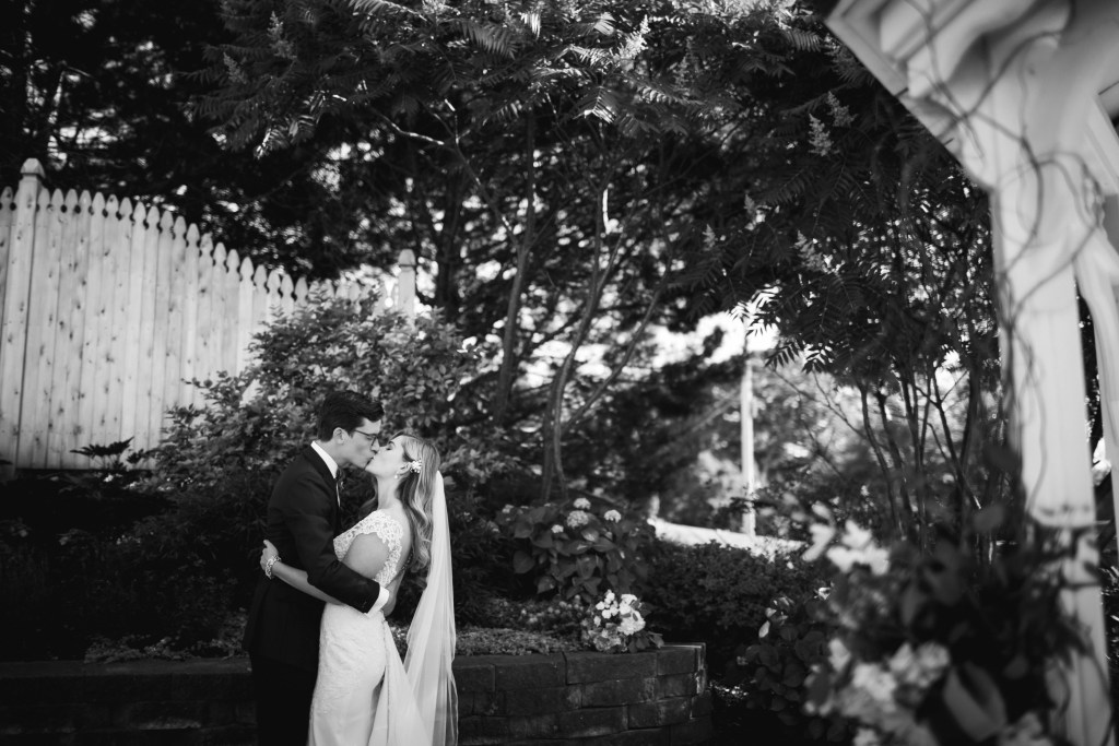 Bride and groom kissing in the garden at The Inn on Peaks Island, Portland Maine.