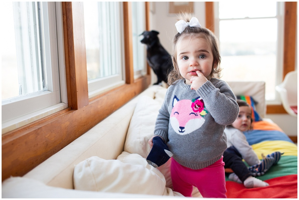 toddler girl wearing sweater with a fox on it and holding one of her brother's socks