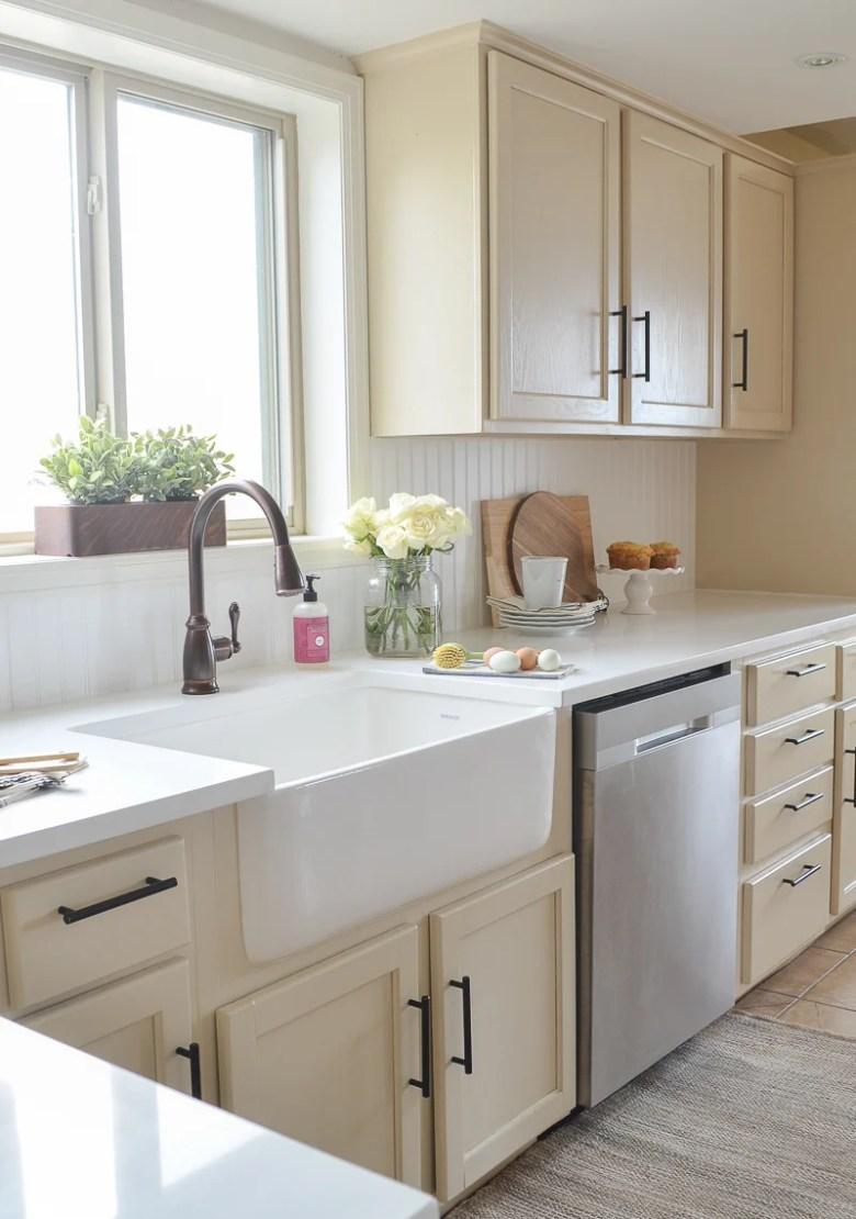 Farmhouse style kitchen makeover with white quartz countertops and farmhouse sink.