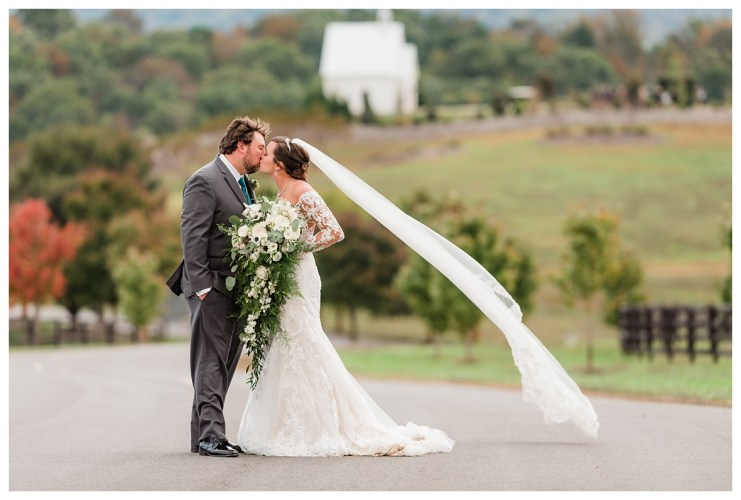 Bride and groom flowing veil with chapel