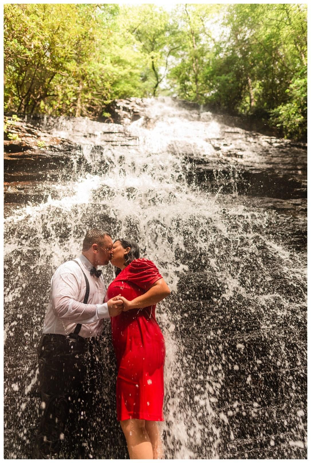 engaged couple kissing under benton falls