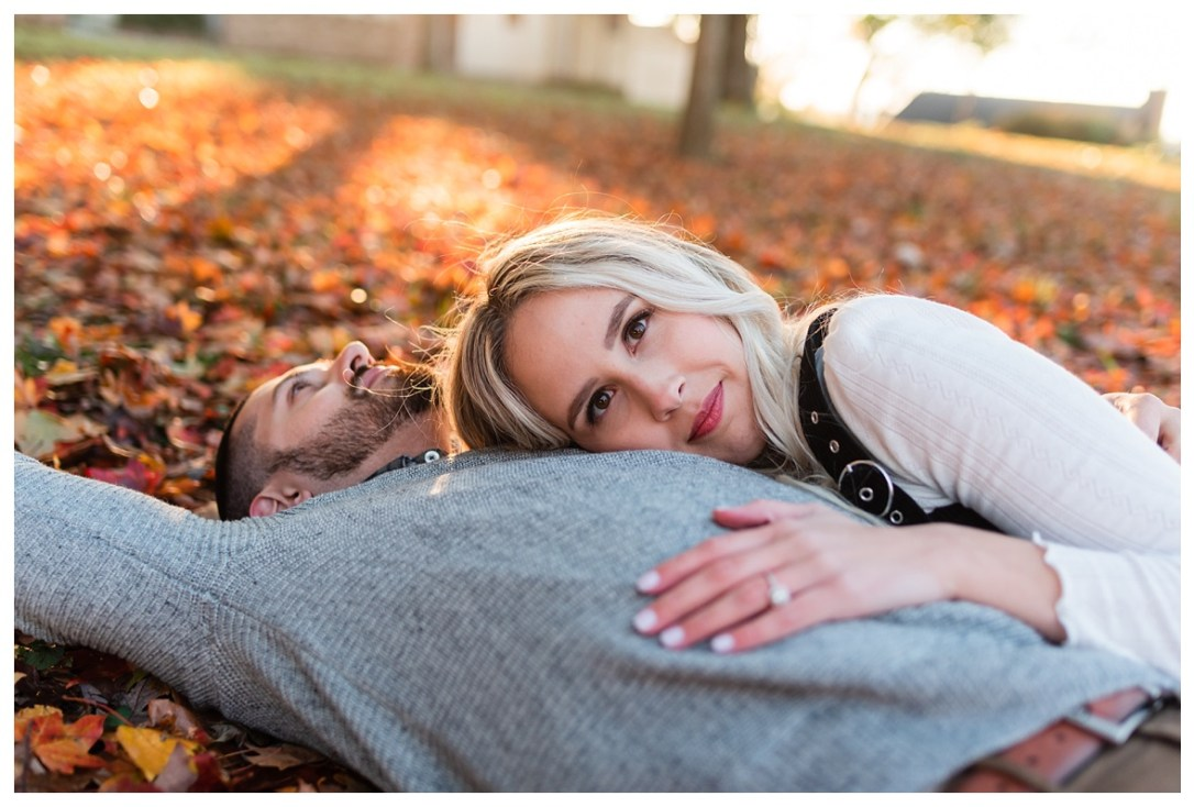 engaged couple rolling in the leaves for fall engagement session