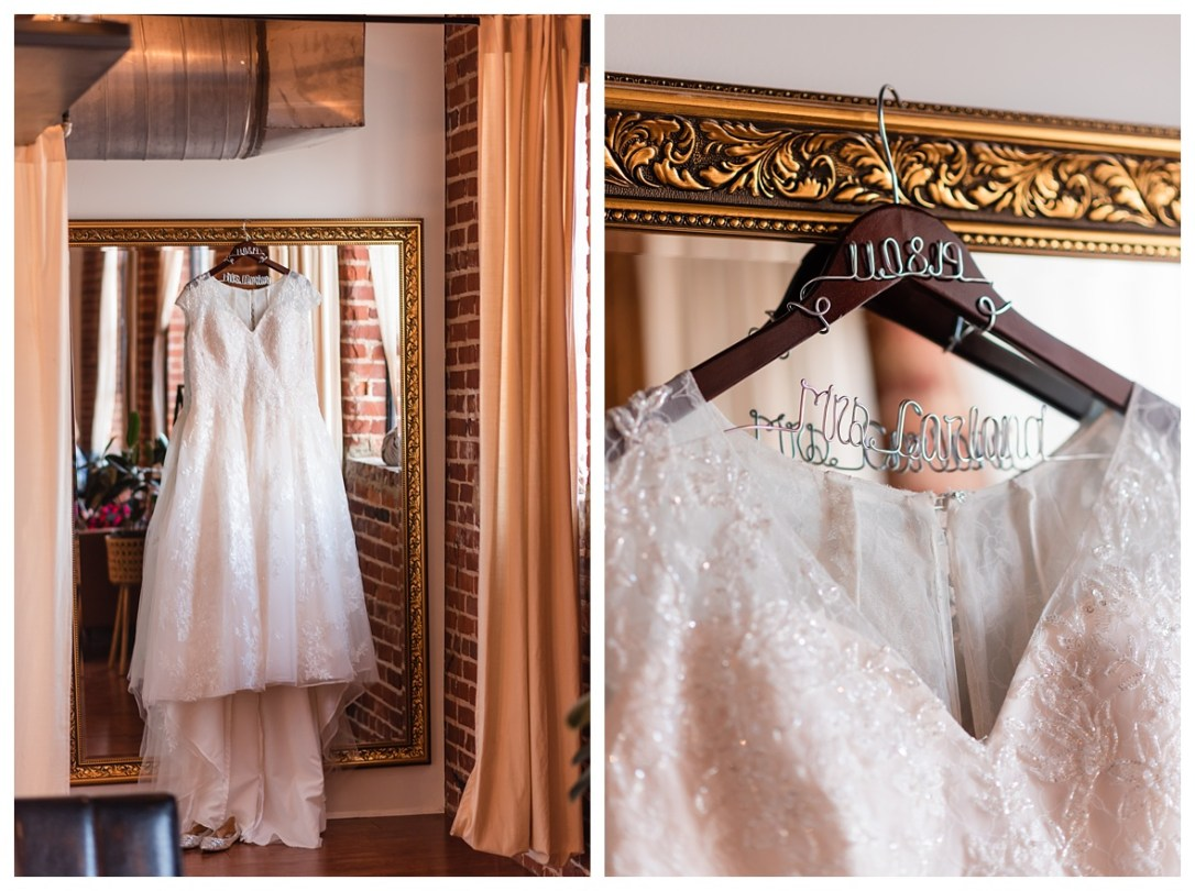 Capped sleeve wedding dress hanging in the mirror