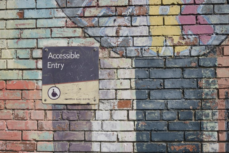 colorfully painted brink wall with a sign that says accessible entry