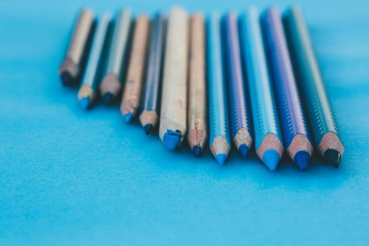 blue, brown, and green colored pencils lying in a line on a blue background, sharpened tips facing toward you