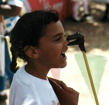 A small child with a dinosaur grabber eating their nose