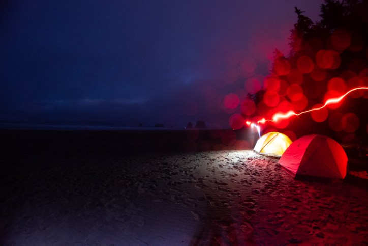 Two tents on a beach, one tent is lit up. Also streaks of red light from where someone with a headlamp is walking.