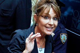 Sarah on bus tour - waving - wearing black jacket and Star of David necklace