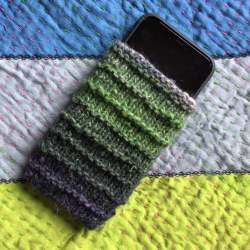 Knit cell phone pouch in green yarn shown on a handsewn quilt