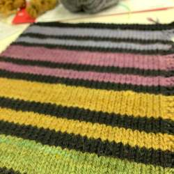 knitted fabric of stripes alternating green, black, yellow, black, rose, black, light blue, black