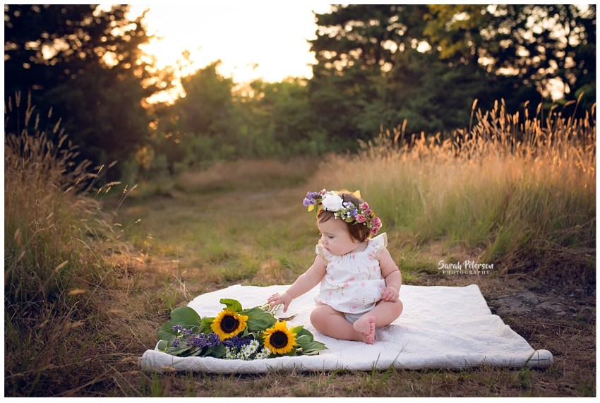 Little baby girl touching wildflowers while sitting on a blanket