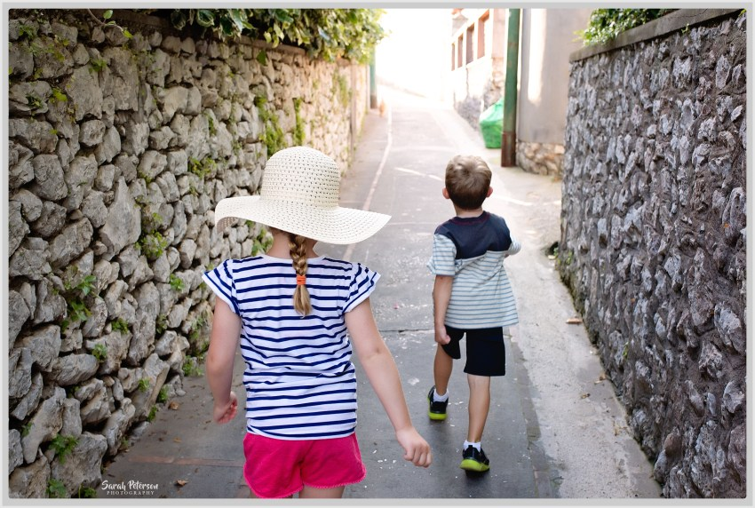 Two kids walking down a narrow road in Anacapri, Italy