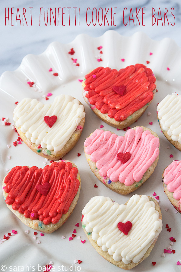 Heart Funfetti Cookie Cake Bars - Love is in the baking with these delightfully chewy, sprinkle filled sugar cookie cake bars topped with fluffy buttercream; show your love for your friends and famiglia with these easy, customizable, heart treats.