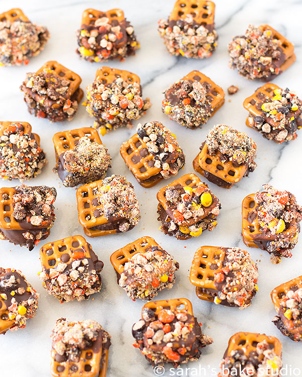 Reese's Peanut Butter Pretzel Bites – Reese's Peanut Butter Cup Miniature sandwiched between two pretzels, dipped in melted chocolate and crushed Reese's Mini Pieces; a sweet and salty, peanut-buttery dream!