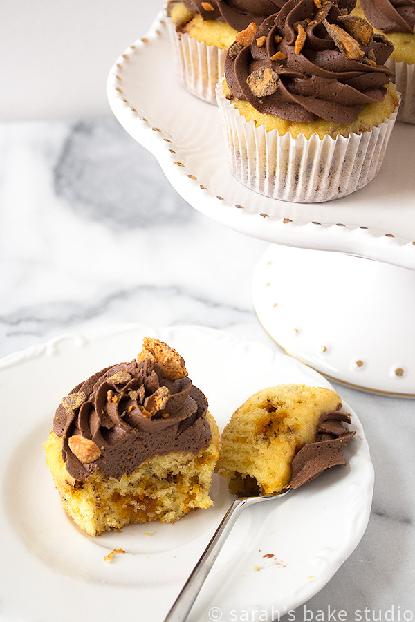 Butterfinger Cupcakes – buttery doctored butter cake mix and Butterfinger Baking Bits baked to cupcake perfection, topped with smooth chocolate buttercream, and sprinkled with bits of Butterfinger happiness!