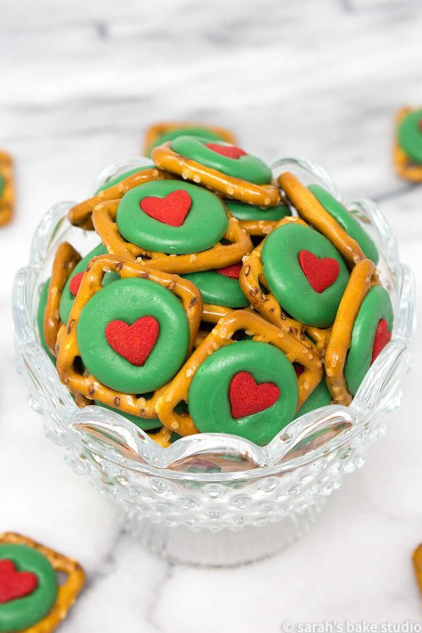 Grinch Pretzel Bites – crunchy pretzel snaps, festive green chocolate wafers, and a delightful red heart quin; a sweet and salty holiday treat that even a Grinch will love.