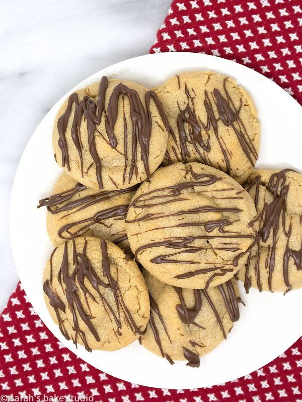 Santas Surprise Cookies – a soft and chewy peanut butter cookie stuffed with a SNICKERS Minis and drizzled with melted milk chocolate; a Christmas cookie MUST!