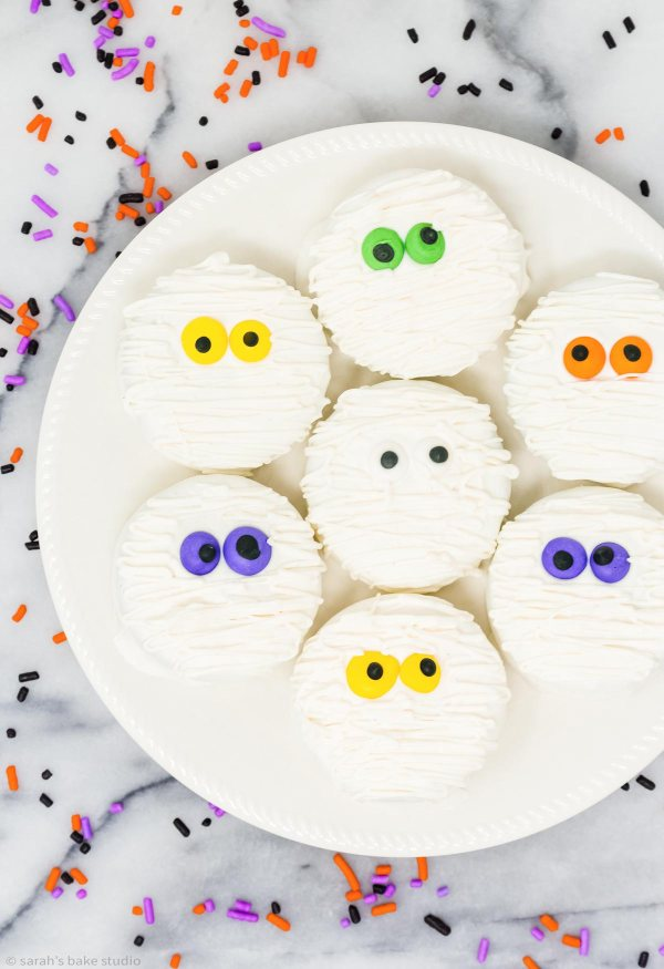 Halloween Mummy Oreo Cookies #Choctoberfest - your favorite Oreo cookies dipped in white chocolate and dressed up as spooky-cute Halloween mummies with royal icing eyes and drizzled with white chocolate.