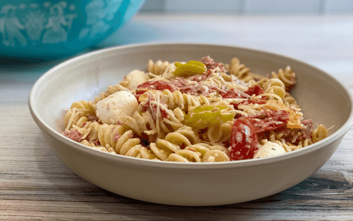 Bowl of pasta salad that contains rotini spiral pasta, fresh mozzarella cheese, parmesan and provolone cheeses, meats, bell pepper, onions, and tomatoes. The bowl is a single serving and sits in front of a serving bowl.