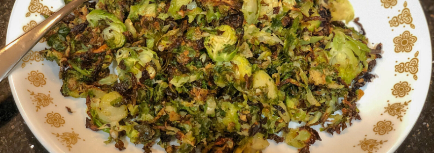 Crispy roasted brussels sprouts on a serving platter with serving fork