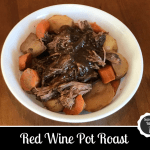Pot roast meat with potatoes and carrots and gravy in a bowl
