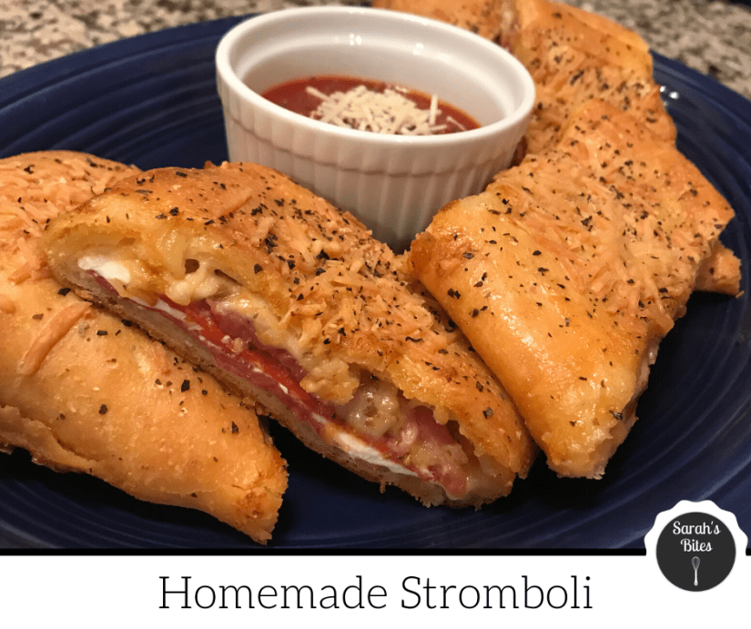 Homemade stromboli cut into slices on a platter with marinara sauce in a ramekin.
