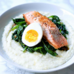 Grits topped with greens, a piece of salmon, and a hard boiled egg cut in half