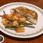 Plate of baked halibut topped with sauce next to roasted potatoes and green beans