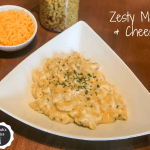 Macaroni and cheese in a dish in front of a bowl of shredded cheddar cheese and a container of elbow noodles