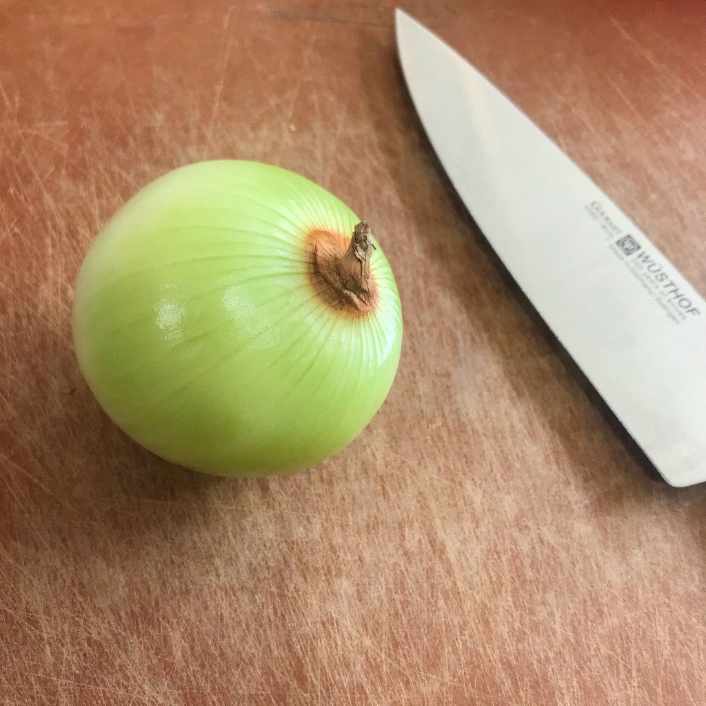Peeled onion next to a knife on a cutting board