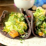 Tacos made with blue corn tortillas filed with potato, lettuce, and cheese, on a plate