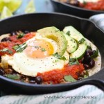Breakfast hash in a cast iron skilled with eggs avocado and tomato