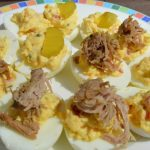 Plate of deviled eggs topped with pulled pork