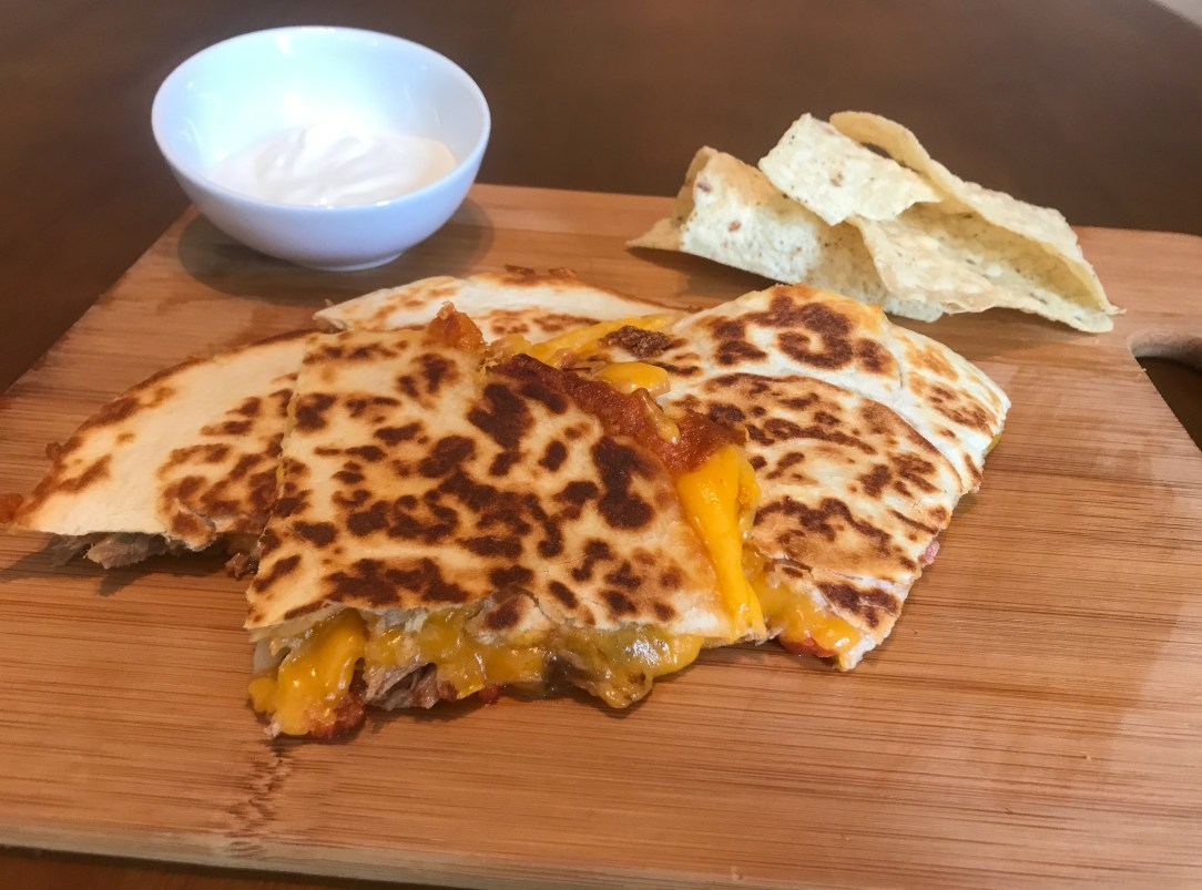 Quesadilla filled with pulled pork and cheddar cheese cut into 4 slices that are stacked on a cutting board. Behind the quesadilla slices is a small bowl of sour cream and a small pile of tortilla chips.