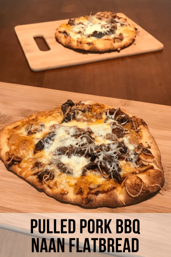 "A small flatbread pizza topped with cheeses and pulled pork on a cutting board. In the background is a second flatbread on a cutting board. Text at the bottom of the image says ""Pulled Pork BBQ Naan Flatbread."""