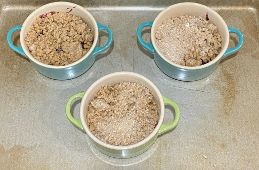 Ramekins with blueberry mixture topped with a crumble