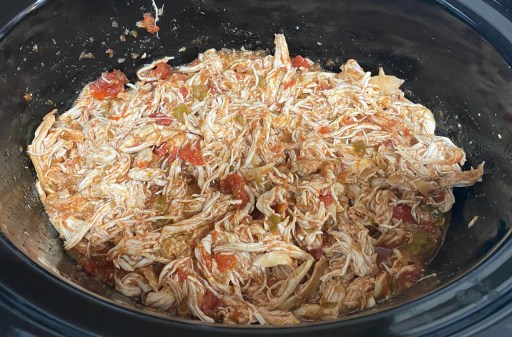 Pulled chicken mixed with salsa in a slow cooker bowl.