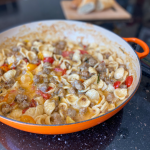 Pan of orecchiette with italian sausage and tomatoes. A few slices of baguette in the background.