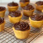 Yellow cupcakes with chocolate frosting on a wire cooling rack.