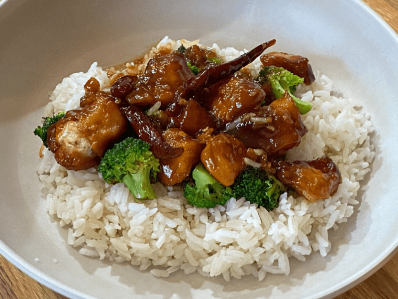 Chicken and broccoli over white rice in a bowl.