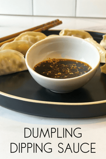 Small bowl of sauce on a plate with steamed dumplings and chopsticks. Text at the bottom of the image says Dumpling Dipping Sauce.
